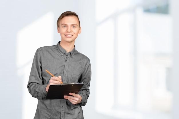 Confiante jovem em camisa fazendo anotações em seu bloco