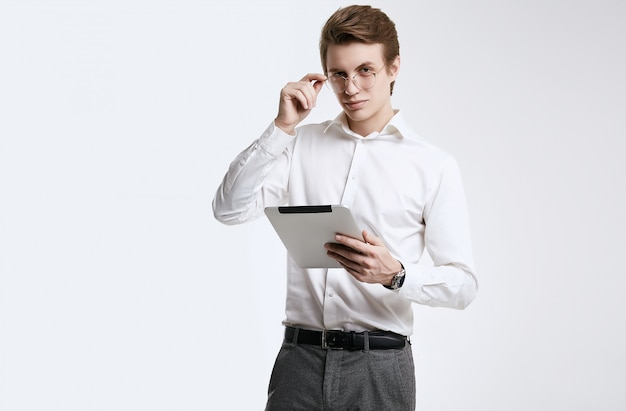 Confiante jovem empresário em camisa trabalhando em tablet digital