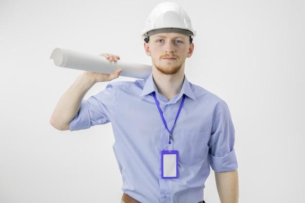 Confiante jovem empresário no capacete branco mantém desenho enrolado no ombro
