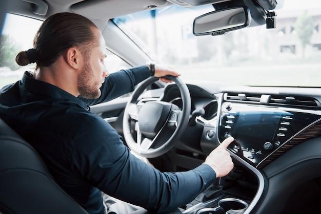 Confiante jovem empresário sentado ao volante do seu carro novo