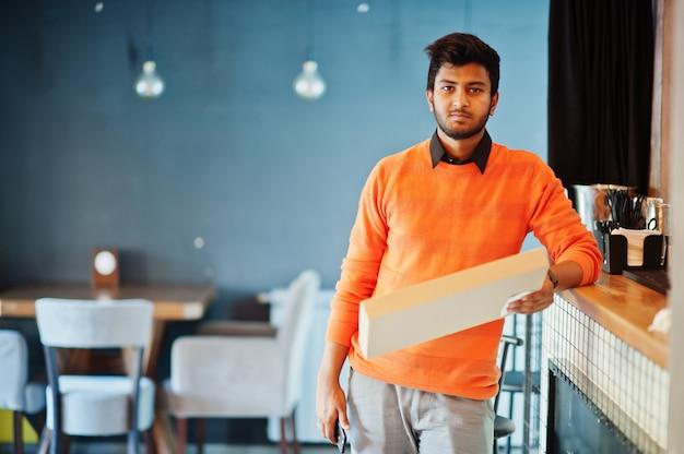 Confiante jovem indiano na camisola laranja em pé perto do balcão de bar no café e segure a caixa para entrega com pizza.