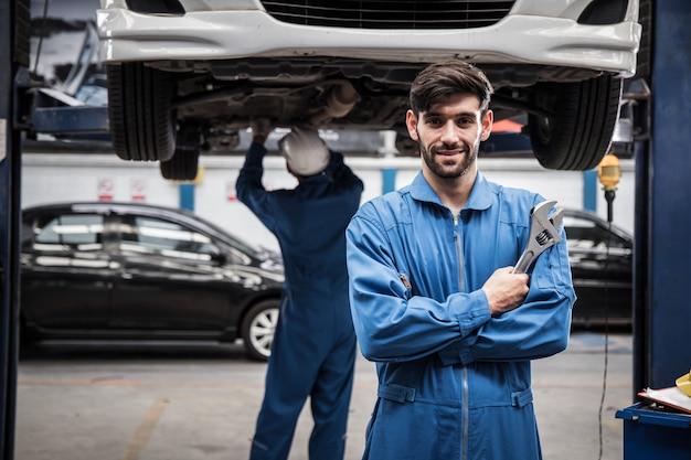 Confiante jovem mecânico em pé com os braços cruzados enquanto colega de trabalho trabalhando.