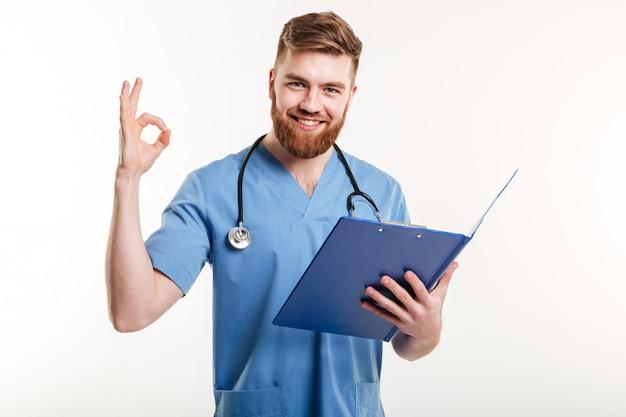 Confiante médico ou enfermeiro com prancheta na mão, mostrando o gesto bem