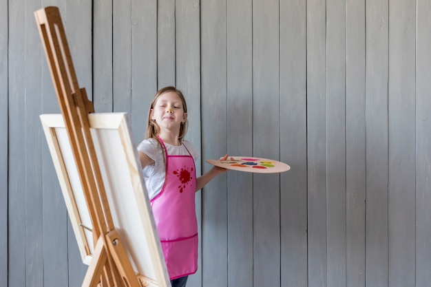 Confiante menina pintura sobre o cavalete de pé contra a parede de madeira cinza