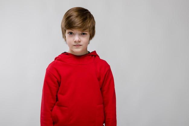 Confiante menino bonitinho caucasiano na camisola vermelha em cinza