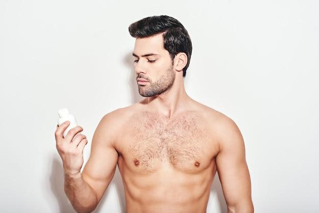 Confiante na pele, lindo homem de cabelos escuros olha para o hidratante que usa em pé
