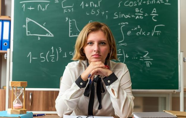 Confiante, olhando para a frente, jovem professora sentada à mesa com o material escolar na sala de aula