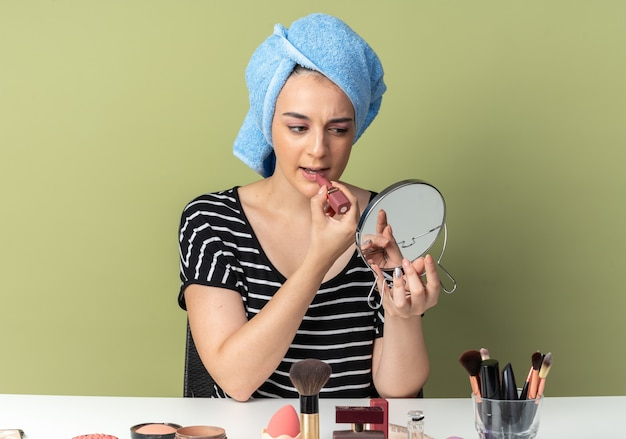 Confiante olhando para o espelho, jovem linda se senta à mesa com ferramentas de maquiagem enroladas em uma toalha, aplicando batom isolado na parede verde oliva