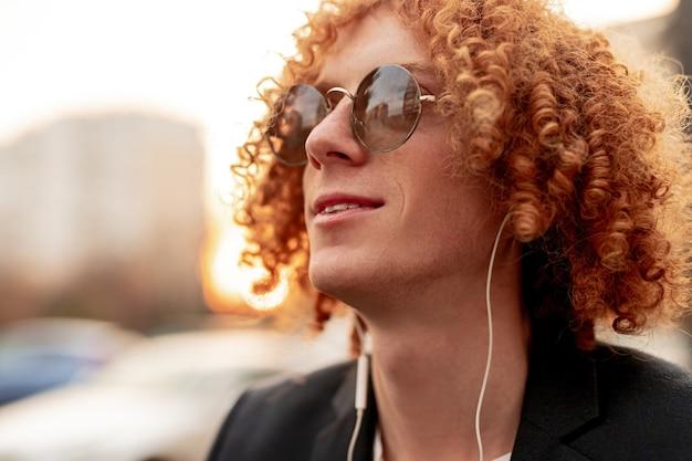 Confiante positivo e elegante cara milenar com cabelo ruivo cacheado em óculos de sol da moda, ouvindo música com fones de ouvido, enquanto descansa em uma rua urbana borrada