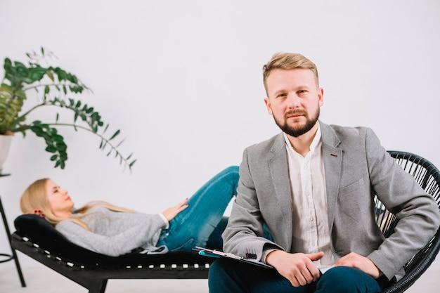 Confiante psicólogo masculino sentado na cadeira na frente de seu paciente do sexo feminino