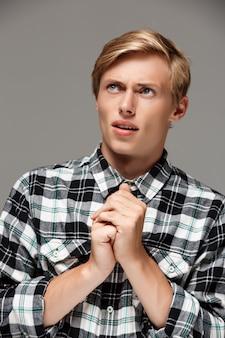 Confiante surpreendeu loiro jovem bonito vestindo camisa xadrez casual com as mãos prontas para rezar olhando para parede cinza