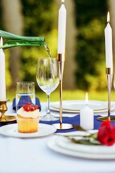 Configuração da mesa, o vinho é derramado de uma garrafa em um copo de vinho, velas e flores no close up da placa, ninguém. talheres de luxo e toalha de mesa branca, talheres ao ar livre