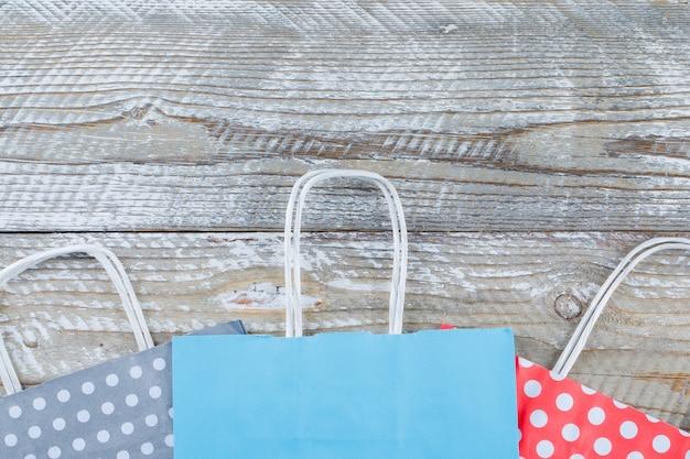 Configuração de aniversário com sacos de presentes de papel no plano de fundo de madeira.