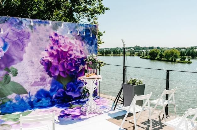 Configuração de casamento. decoração. cadeiras de madeira na área de banquetes do quintal. arco para cerimônia de casamento decorado com flores e verdes, folhagens.