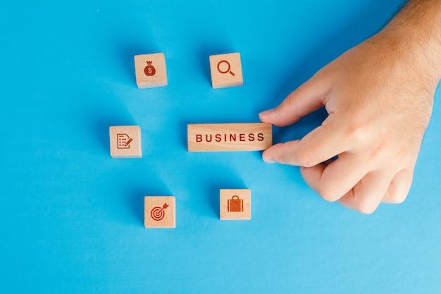 Configuração de conceito de negócio com ícones em cubos de madeira na mesa azul plana. mão segurando o bloco de madeira.