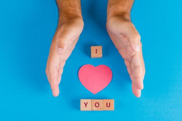 Configuração de conceito de relacionamento com cubos de madeira na mesa azul plana. mãos protegendo papel cortado coração.