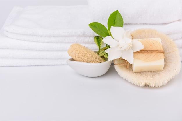 Configuração de conceitos de spa e cuidados de saúde com pilha de toalhas brancas e esfoliante de luffa com sabonete de leite com flores tropicais de gardênia em fundo branco