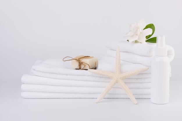 Configuração de conceitos de spa e saúde com pilha de toalhas brancas estrela de peixe e flores tropicais de gardênia, sabonete de leite, esfoliante luffa na superfície branca