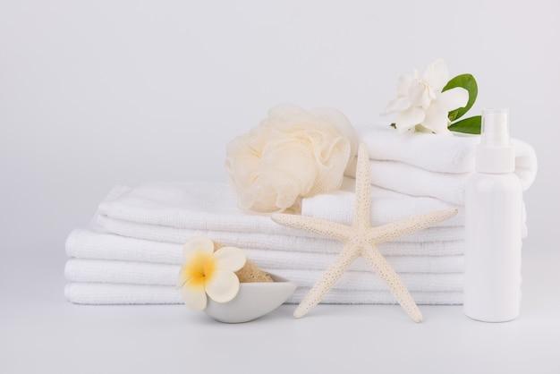 Configuração de conceitos de spa e saúde com pilha de toalhas brancas estrela-peixe, flores de gardênia, frasco de spray e esfoliante bucha na superfície branca