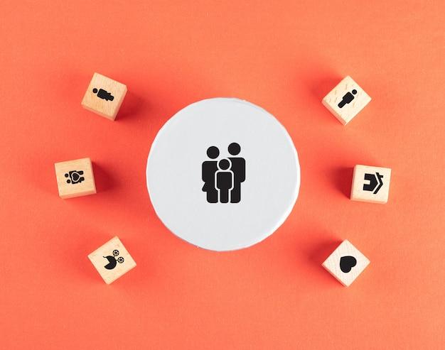 Configuração de família com ícones em cubos de madeira na mesa vermelha plana.