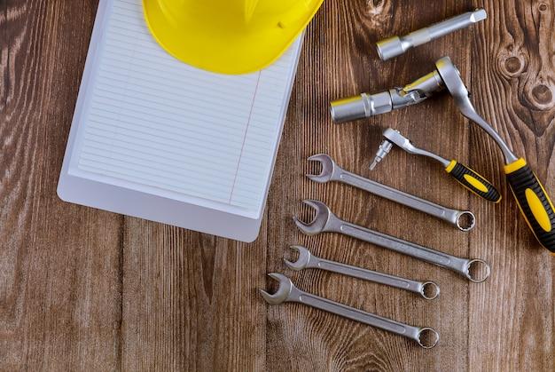 Configuração de ferramentas para mecânico de automóveis, capacete de segurança amarelo na chave de boca automóvel espiral bloco de notas madeira fundo