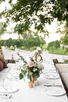 Configuração de mesa de casamento decorada com flores frescas em um vaso de latão.