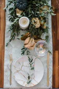 Configuração de mesa de halloween em fundo escuro. prato com doces s sobre uma mesa escura com abóbora preta e dourada. conceito de férias da moda de vista superior plana leigos.