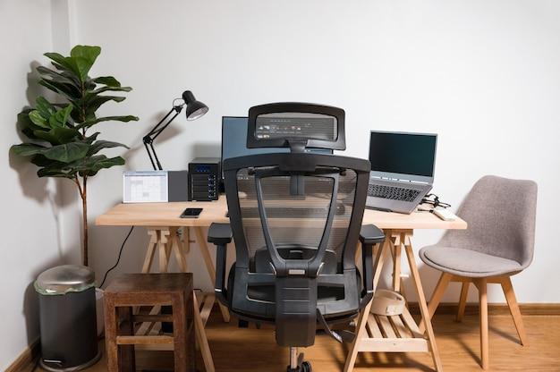 Configuração de mesa de madeira com laptop, monitor, mouse, abajur, cadeira ergonômica e árvore artificial no local de trabalho no quarto