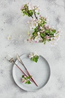 Configuração de mesa de mesa de primavera com florescimento de galhos de macieiras e flores na mesa de luz. decoração de festas em estilo provençal. jantar romântico. sobrecarga com espaço de cópia para o texto