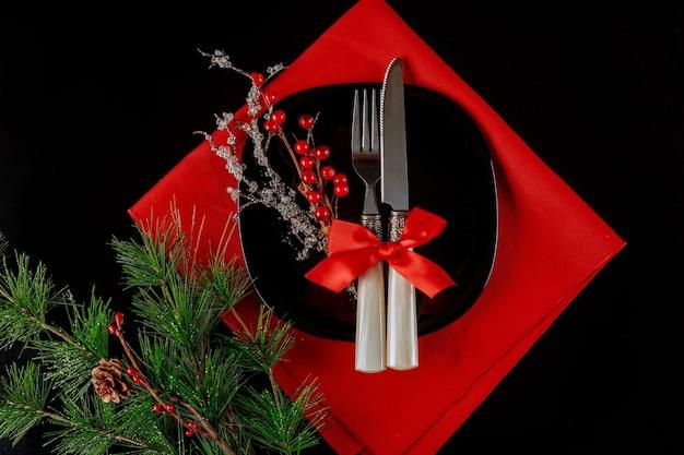 Configuração de mesa de natal com decoração em fundo preto.