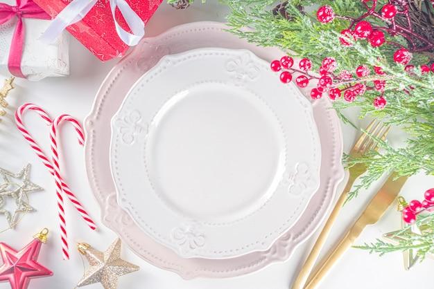 Configuração de mesa de natal com pratos vazios, caixa de presente e decoração de natal. vista superior plana com espaço de cópia, fundo branco