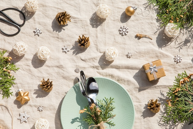 Configuração de mesa de natal. decorações de natal com prato e talheres, decoração de ouro e pinhas na toalha de mesa vintage