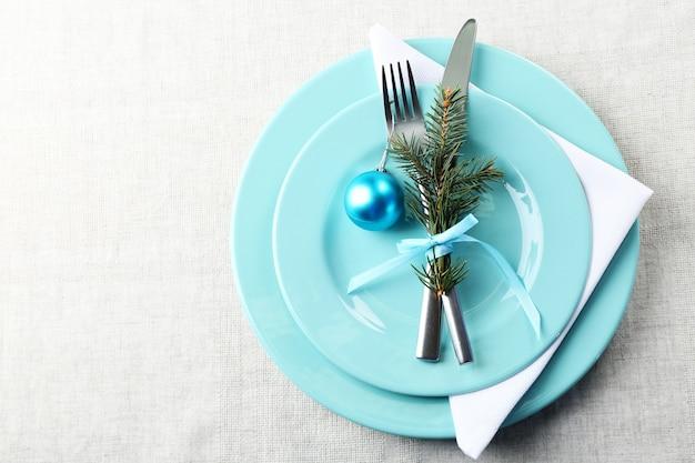Configuração de mesa de natal elegante em azul e branco em fundo cinza de toalha de mesa