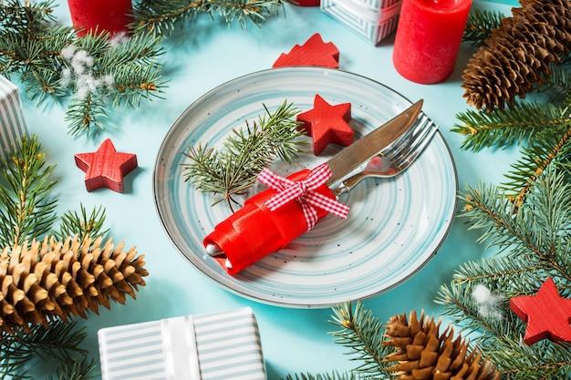 Configuração de mesa de natal em fundo azul com árvore do abeto e decoração.