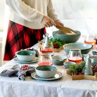 Configuração de mesa de natal rústica com talheres de cerâmica artesanais, pratos e tigelas, decorações de anjo de natal na toalha de mesa branca em frente à janela. mulher segurando uma saladeira