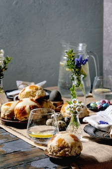 Configuração de mesa de páscoa com ovos coloridos e de chocolate, pãezinhos cruzados, buquê de flores, prato de cerâmica vazio com guardanapo, copo de limonada na mesa de madeira com toalha de mesa têxtil.