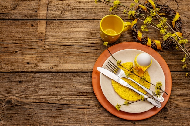 Configuração de mesa de páscoa em fundo de madeira velha. modelo de cartão de férias de primavera. talheres, guardanapo de crochê, ovo, raminhos de flores de dogwood, xícara, grinalda
