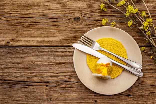 Configuração de mesa de páscoa em fundo de madeira velha. modelo de cartão de férias de primavera. talheres, guardanapo de crochê, ovo, ramos de flores de dogwood