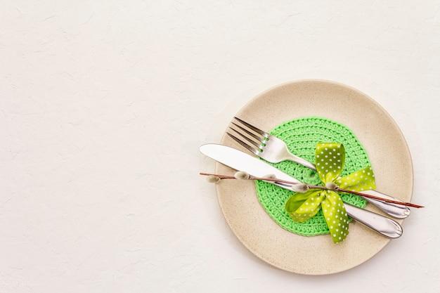 Configuração de mesa de páscoa em plano de fundo texturizado branco massa de vidraceiro. modelo de cartão de férias de primavera. talheres, guardanapo de malha, laço, selos de salgueiro
