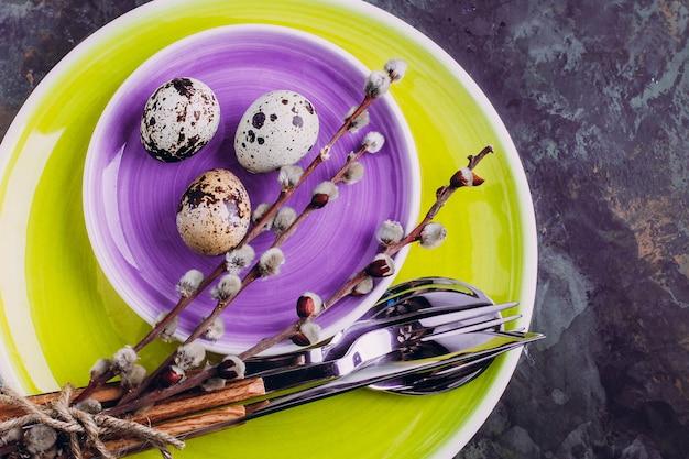 Configuração de mesa de páscoa. placa amarela e roxa, talheres, ovos de codorna e salgueiro