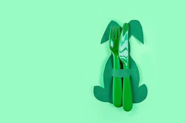 Configuração de mesa de páscoa. porta-talheres criativo engraçado bonito em forma de coelho verde sobre fundo verde. diy e criatividade infantil. fundo de páscoa com espaço de cópia para o texto.