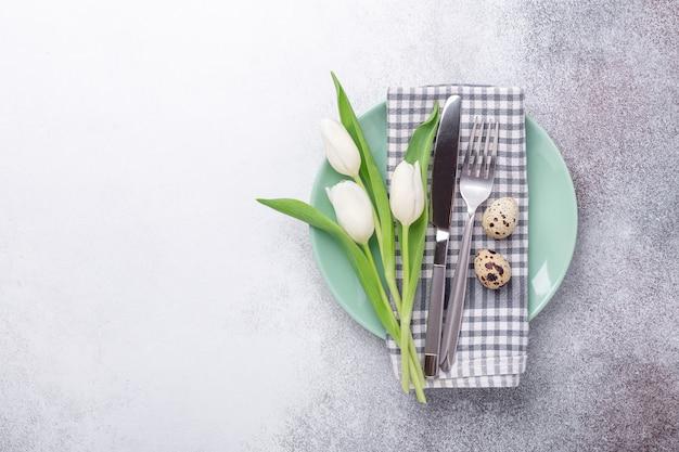 Configuração de mesa de páscoa. pratos vazios de hortelã e brancos, guardanapo de linho, tulipas brancas e ovos de codorna em fundo de pedra - imagem