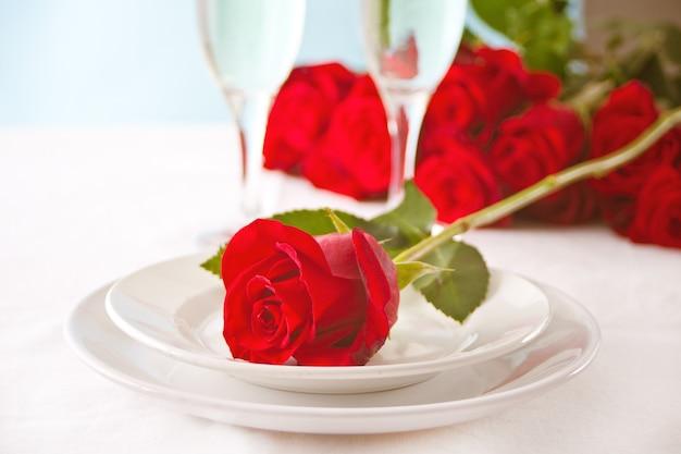 Configuração de mesa de restaurante romântico para dois com rosas no prato.