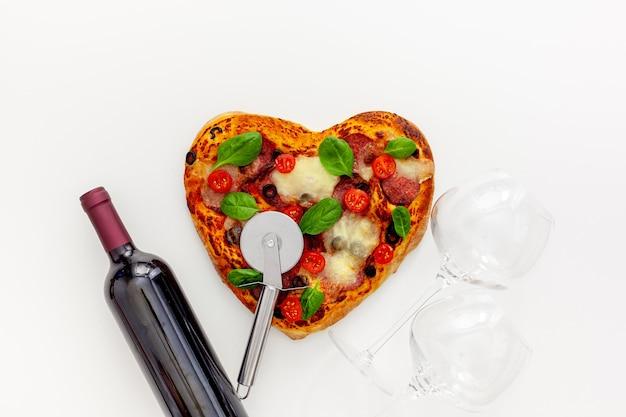 Configuração de mesa do dia dos namorados. pizza de coração com vinho e taças