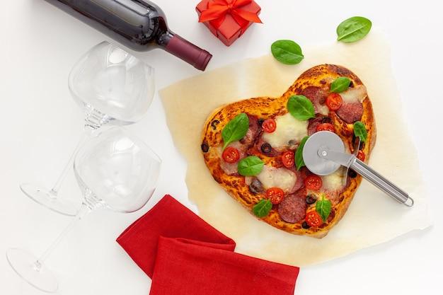 Configuração de mesa do dia dos namorados. pizza de coração com vinho, taças e caixa de presente