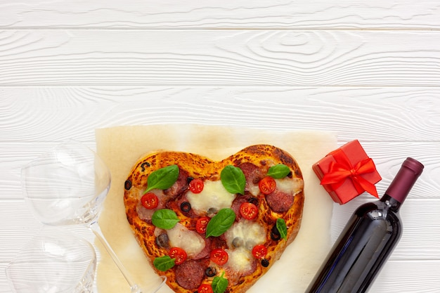 Configuração de mesa do dia dos namorados. pizza de coração com vinho, taças e caixa de presente Foto Premium