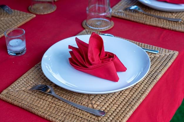 Configuração de mesa elegante com garfo, colher, prato branco e guardanapo vermelho no restaurante, close-up. bela mesa de jantar posta com talheres e guardanapos arranjados