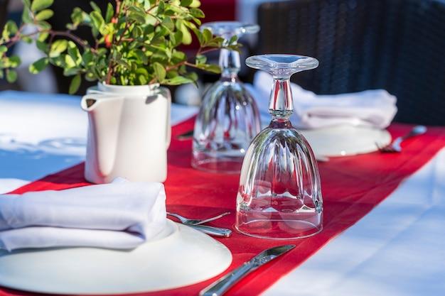 Configuração de mesa elegante com garfo, faca, copo de vinho, prato branco e guardanapo vermelho no restaurante. bela mesa de jantar posta com talheres e guardanapos arranjados para o jantar, turquia