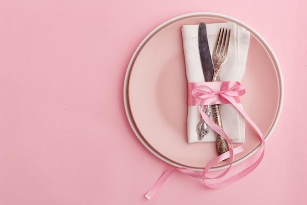 Configuração de mesa elegante e elegante. faca e garfo em um guardanapo em um prato em uma superfície rosa.