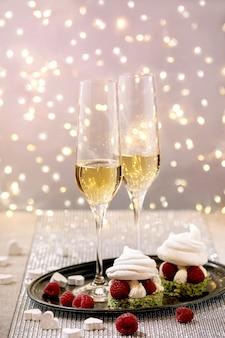 Configuração de mesa festiva com duas taças de champanhe e sobremesas de merengue de baga na bandeja em pé na mesa prateada cintilante, corações brancos, luzes de bokeh